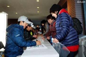 集まったギャラリーにサインをする石川遼ら(大会提供)