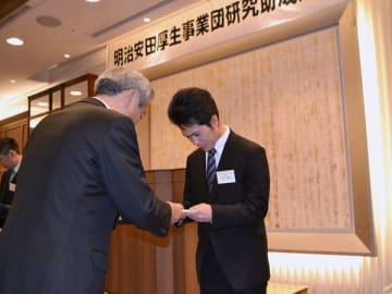 【中熊理事長(左)から目録を受け取る中川さん(右)=都内で】