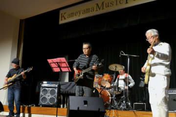 【熱演するアマバンド「プレシャス・ブルー」の4人=亀山市東御幸町の市文化会館で】