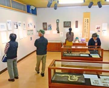 翁長さんが残した言葉やゆかりの品に見入る来場者=名護市・名護博物館ギャラリー