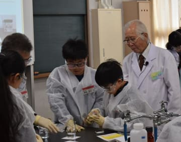 参加者の実験を見守る白川さん(右端)=15日、千葉市中央区の千葉県立千葉工業高校