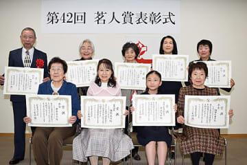 賞状を手に喜ぶ受賞者ら=15日、鳥取市富安2丁目の新日本海新聞社
