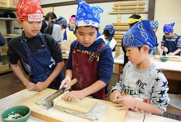 包丁で生地を切って麺にする子どもたち=15日、倉吉市関金町明高の水車の郷体験工房