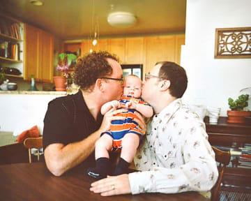 会場に展示された1枚で赤ん坊にキスをするゲイのカップルの写真