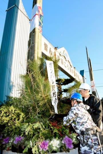 復興を願い大門松を設置する中筋地区の住民=15日午後、西予市野村町野村