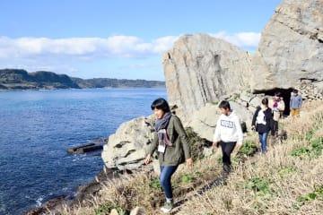 湊地区のPR動画を作るために立神岩を見学する中高生ら=唐津市湊
