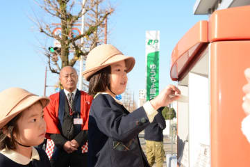 ポストに年賀状を投かんする若楠幼稚園の園児たち=佐賀市の佐賀中央郵便局
