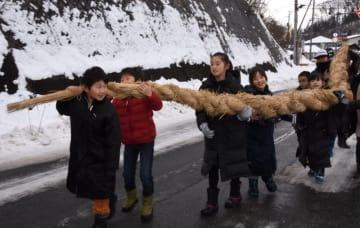 完成した6・5メートルのしめ縄を協力して運ぶ子どもたち