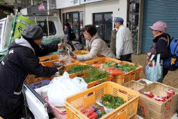 軽トラックに積まれた新鮮な野菜を買い求める客