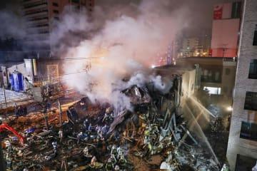 爆発し崩れ落ちた建物。周囲に木片などが散乱する中で消火活動が続けられた=16日午後10時46分、札幌市豊平区