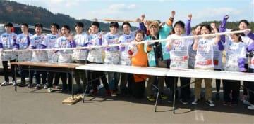 長さ5・12メートルのきりたんぽを作り上げ、喜ぶ学生ら=11月11日、大館市曲田