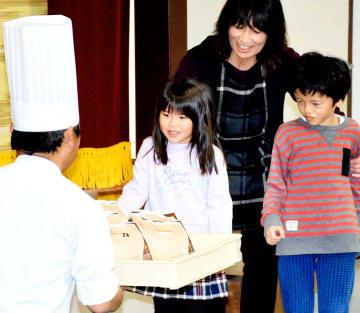 ケーキの入ったトレーを受け取る野村保育所の園児