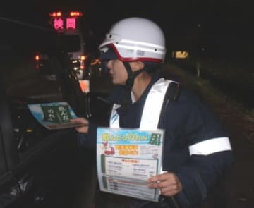 一斉取り締まりで、ドライバーが飲酒運転をしていないか調べ、チラシを配布する大分東署員