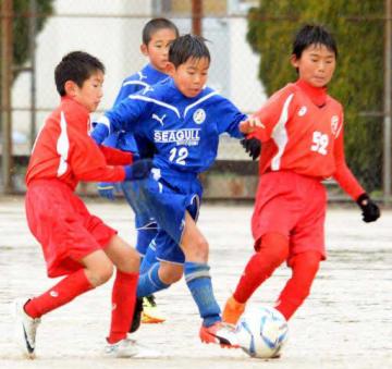 雨が降る中、決勝戦で懸命に競り合うシーガル広島(青のユニホーム)とレヴァリーズ広島FCの選手