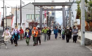 【朝から11キロの熊野古道を歩き、最終地点の闘鶏神社に到着した一行。周辺の景色や町並みに目をやりながら境内へと進んだ(16日、和歌山県田辺市東陽で)】