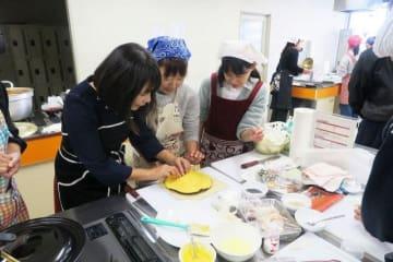 長谷川さん(左)の手ほどきを受けおせち料理を作る参加者=横浜市神奈川区