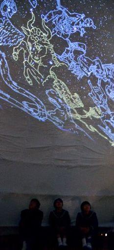 さかもと八竜天文台が製作した移動式プラネタリウムで、星座の絵を眺める生徒ら=八代市