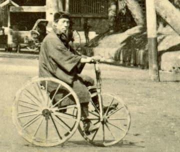 東京・芝の増上寺前で三輪自転車に乗り、カメラ目線でポーズを取る男性(「大教院山門」の一部を拡大、日本カメラ博物館所蔵)
