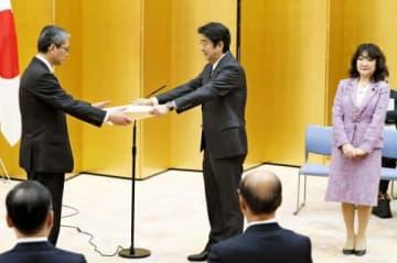 安倍首相(中央)から「女性が輝く先進企業」の内閣総理大臣表彰を受ける新日本科学の永田良一社長=首相官邸