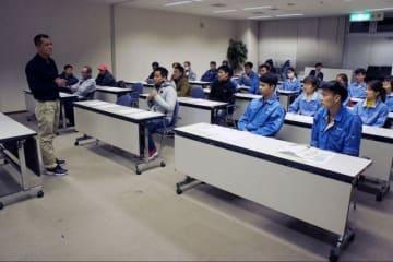 若手のベトナム人従業員に日本のものづくりのポイントなどを伝えるイサ・ゴジャレイさん(左)=綾瀬市役所