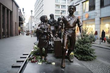 17日、ベルリンにある「キンダートランスポート(子ども輸送)」の像のそばを歩く人々(AP=共同)