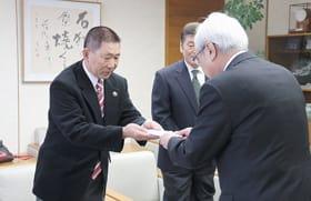 菊谷市長に寄付を手渡す実行委員長の大楽さん(左)ら