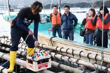ワインボトルを海中に沈める様子を見守る参加者