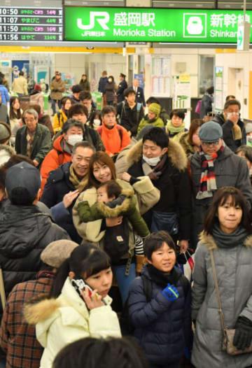 新幹線の改札口付近で、家族や知人との久しぶりの再会に笑顔を見せる帰省客=2017年12月29日、盛岡市・JR盛岡駅