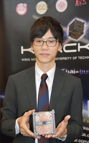 自ら製作した人工衛星の模型を持つキングモンクット工科大のポンサトーン・サイスッチャリット講師=18日、バンコク(共同)