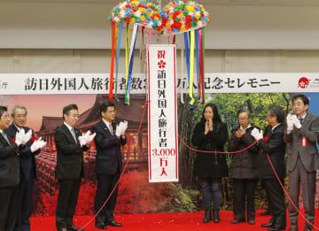 訪日外国人旅行者の3千万人突破を記念し、関西空港で開かれた式典。中央左は石井国交相、同右は台湾から訪れた王劭予さん=18日午後