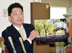 「1・17のつどい」東京会場の詳細について、日比谷公園の写真パネルを示しながら話す藤本真一委員長=18日午前、神戸市役所