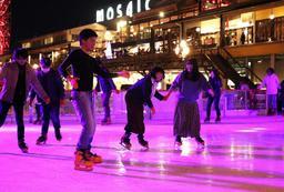 鮮やかな光に包まれ、スケートを楽しむ人たち=18日夜、神戸市中央区東川崎町1