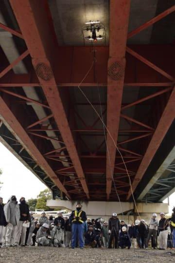 コンクリート床板をドローンを使って試験的に点検した見学会=18日、松山市出合