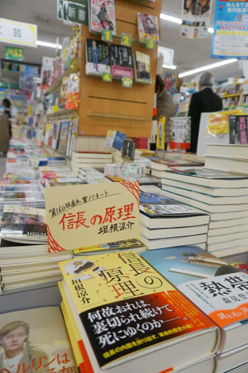 手書きの宣伝カードを添えて平積みされた垣根涼介さんの候補作「信長の原理」=諫早市、明光堂書店