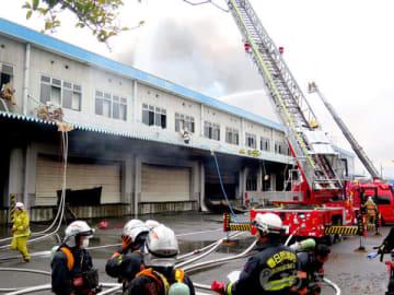 倉庫火災で消火活動を続ける消防隊員ら=3月9日正午ごろ、加須市新利根1丁目