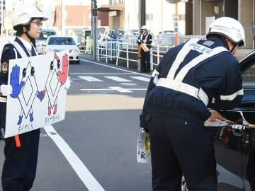 「ダイヤくん」と「ダイヤちゃん」のパネルを使って注意を呼び掛ける警察官ら=岐阜市薮田南