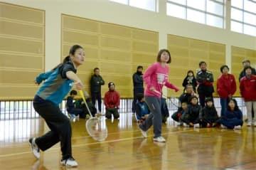 麦島校区の住民が観戦する中、中学生と対戦する垣岩令佳さん(左)、藤井瑞希さん=八代市