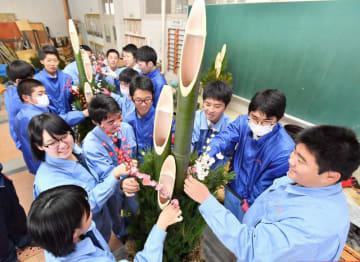 「門松で福を届けよう」。被災地に思いをはせ、笑顔で作業する生徒たち=18日、花巻農高