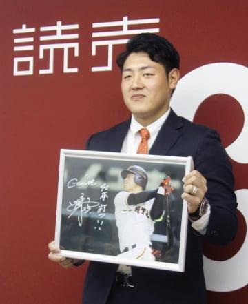 契約更改交渉を終え、記者会見で来季の目標を書き込んだ自身の写真を手にする巨人の岡本=19日、東京・大手町の球団事務所