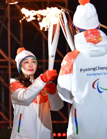 2018年3月、平昌冬季パラリンピックの聖火リレーで、聖火を引き継ぐキム・ヨナさん(共同)