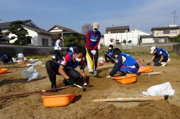 土砂を掘り起こしてガラス片などを取り除く学生ら=岡山県倉敷市真備町(長崎国際大提供)