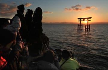 鳥居の内側に昇る朝日を狙い、肩を寄せ合って撮影する写真愛好家たち(19日午前7時10分、滋賀県高島市鵜川)