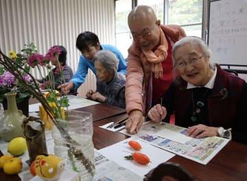 絵手紙制作を楽しむ松野さん(右)、中山さん(右から3人目)。講師の石本さん(右から2人目)が笑顔で指導する=長崎市、エスポアールそとめ