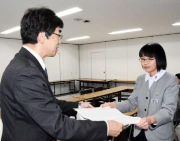 古舘和好市長公室長(左)に提言書を手渡す谷藤沙帆さん