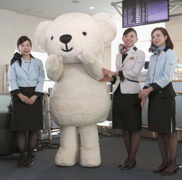 一新された制服で記念撮影に応じる客室乗務員らと熊のマスコットキャラクター「ベア・ドゥ」=20日午前、羽田空港