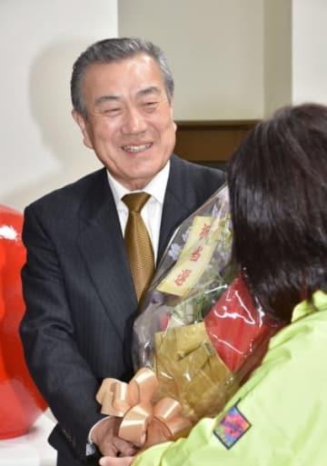無投票で初当選を決め、花束を受け取る主浜了氏=11月4日