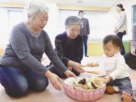 室蘭市子育て世代包括支援センターに布製遊具を寄贈し子どもと触れ合う(左から)細野代表と半沢さん