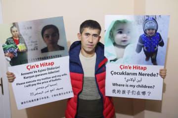 拘束されたとされる母と妻や、行方不明の2人の子どもの写真を掲げるアブドゥルラフマン・ハサンさん=11月、トルコ・イスタンブール(共同)
