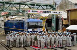 累計製造5千両目の機関車を背に並ぶ川崎重工業兵庫工場の従業員ら=神戸市兵庫区
