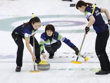 女子1次リーグ ロシアのチームと対戦し、ショットを放つ北海道銀行の吉村。左は近江谷、右は小野寺=軽井沢アイスパーク